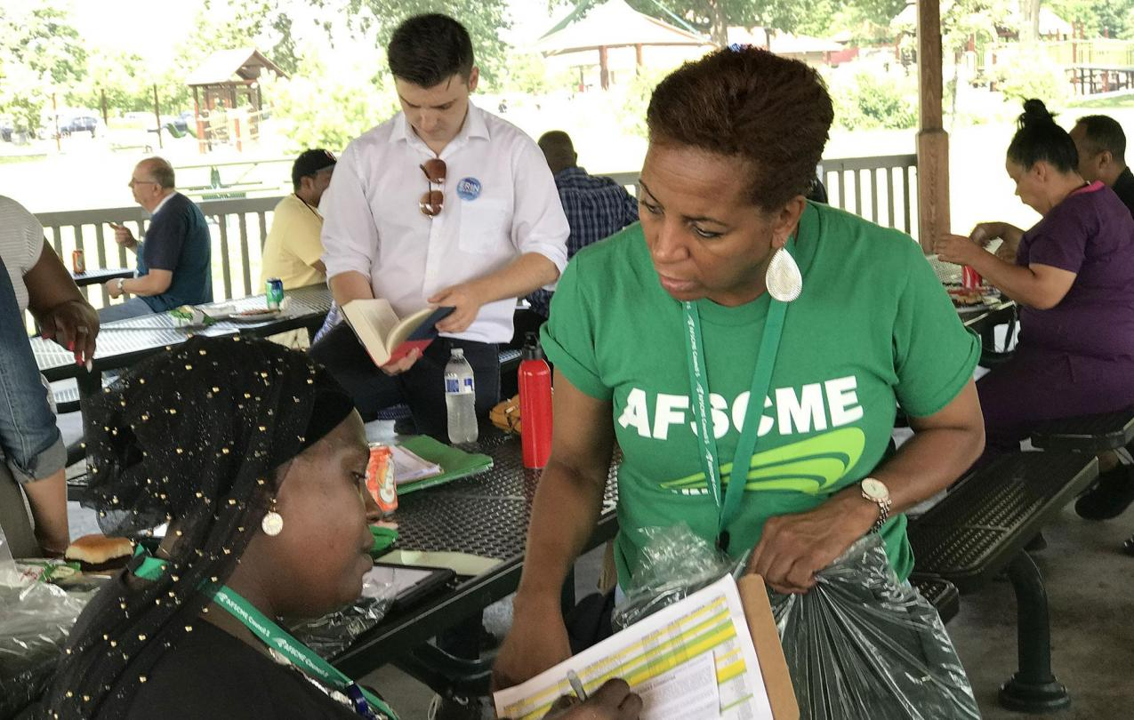 Fatmata Turay signs a PEOPLE card as member organizer Starr Suggs waits to award Turay with a new PEOPLE jacket.
